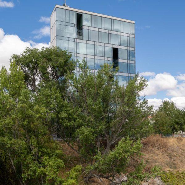 fotografia de arquitectura edificio detras de arboles y rio