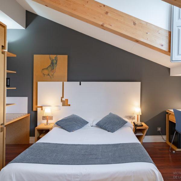 hotel el coloquio de los perros habitacion abuhardillada con cama y escritorio