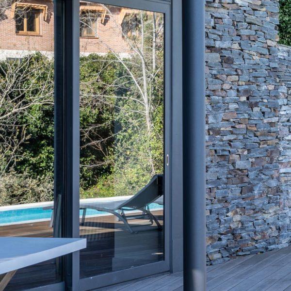 detalle de banco con reflejo de piscina en ventana
